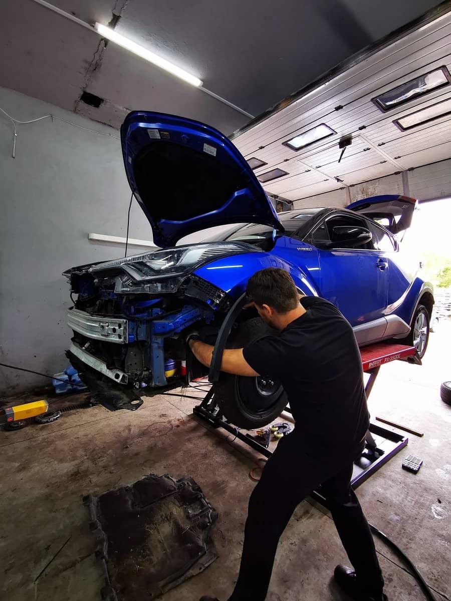 mechanik samochodowy na warsztacie samochodowym przeprowadza naprawę z użyciem podnośnika nożycowego