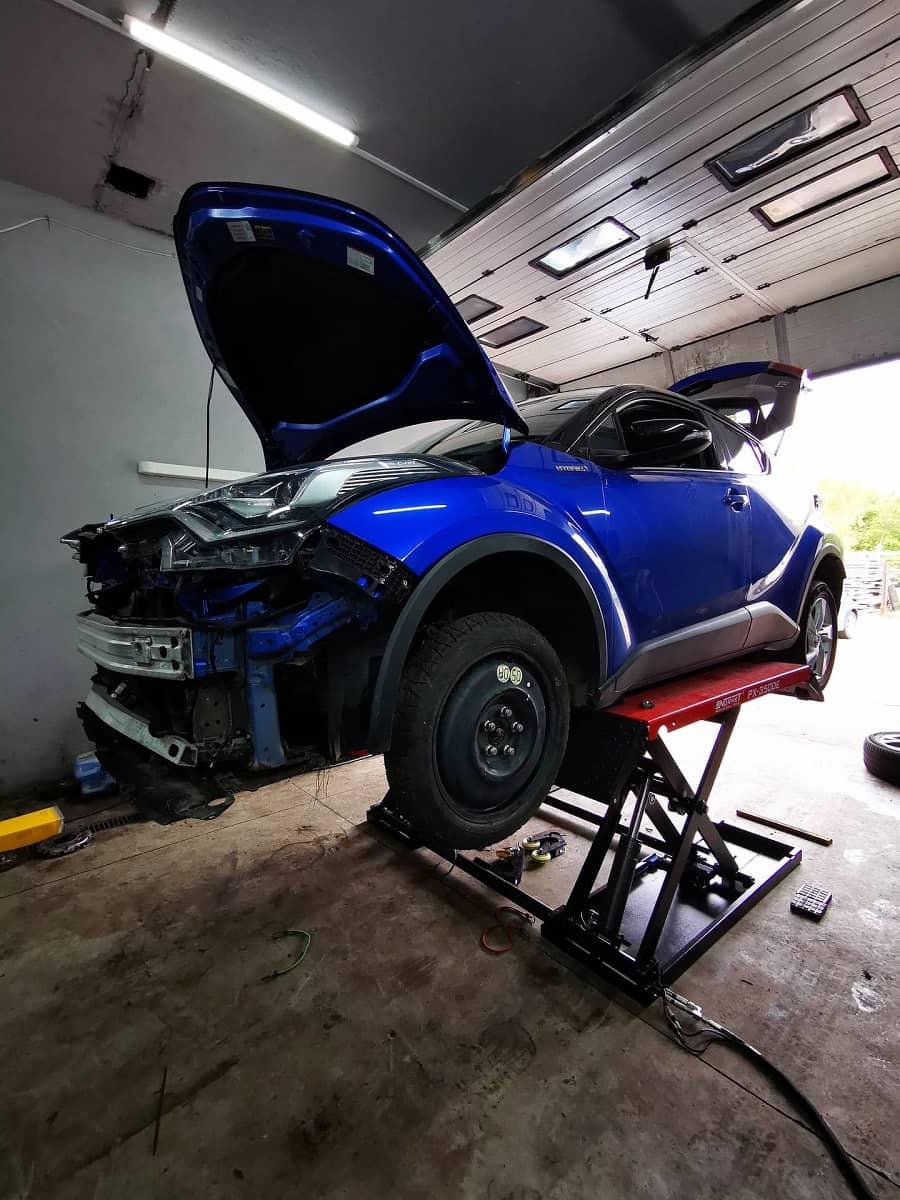 mechanika samochodowa na warsztacie samochodowym przy użyciu podnośnika nożycowego